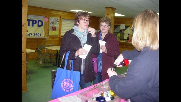 Lori Petzel and Audrey Oehlke taste some Winneshiek Wildberry Winery from Beth Guzman.